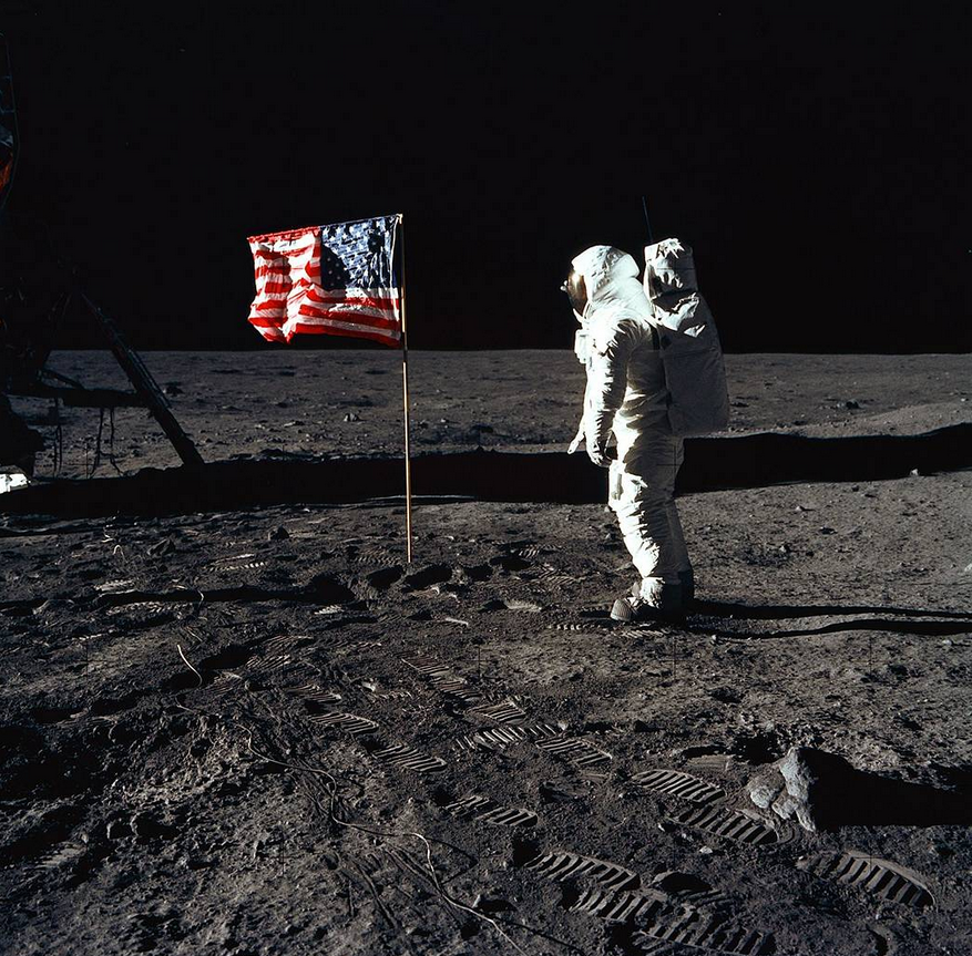 Aldrin poses beside the Lunar Module and flag during an extravehicular activity (EVA).