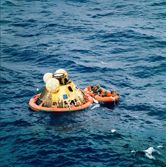 Apollo 11 crew await pickup by a helicopter from the USS Hornet, prime recovery ship.